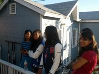 The girls watching the batting cage