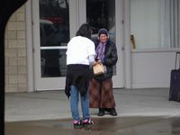 Athena handing out a bag lunch to a homeless lady