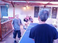 Ryan schooling Les at ping-pong while the girl's sing crazy songs